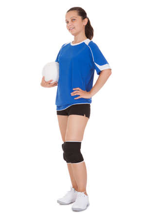 hands on hip: Happy female volleyball player holding ball on white