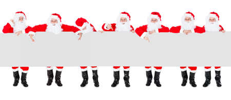 Group Of Happy Santa Claus Holding Christmas Poster Banner Over White Background photo