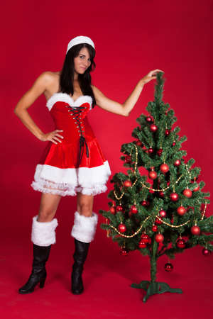 Beautiful Woman Wearing Santa Claus Costume Standing Near Christmas Tree Stock Photo - 22752879