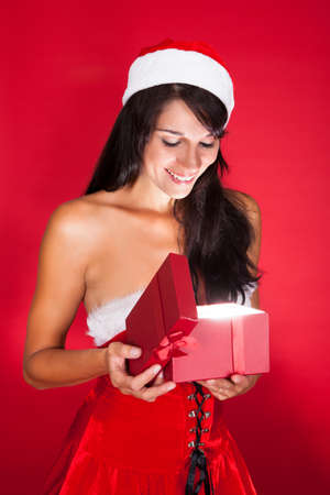 Happy Woman Opening Christmas Gift Isolated Over Red Background Stock Photo - 22752881