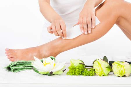 waxing: Beautician Waxing A Womans Leg In Spa Stock Photo