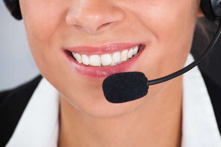 Happy Young Female Callcenter Employee Wearing Headset In Office Stock Photo - 22752949