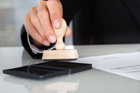 rubber stamp: Close-up Of Business Man Hand Pressing Rubber Stamp On Document Stock Photo