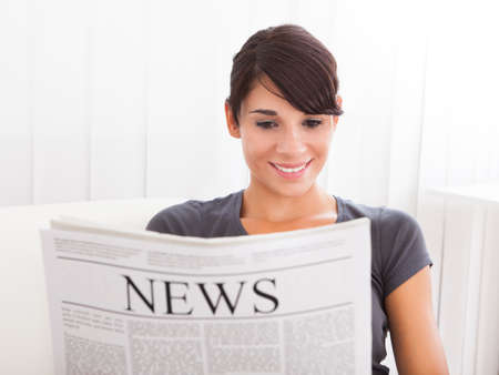Young Happy Woman Reading Newspaper On Couch photo