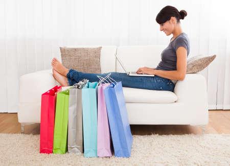 chicas comprando: Hermosa mujer joven sentada en el sof� de compras en l�nea