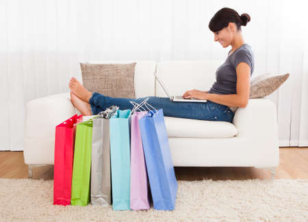 commerce communication: Young Beautiful Woman Sitting On Couch Shopping Online