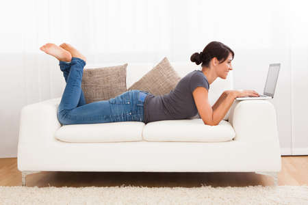 Beautiful Young Woman On A Sofa Working With A Laptop Stock Photo