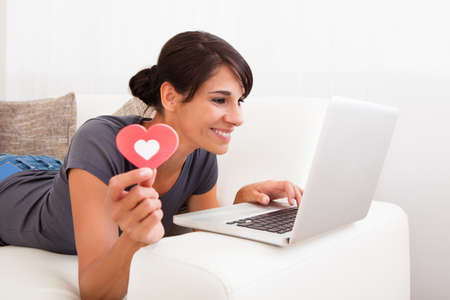 Young Happy Woman Showing Heart Shape While Using Laptop On Couch photo