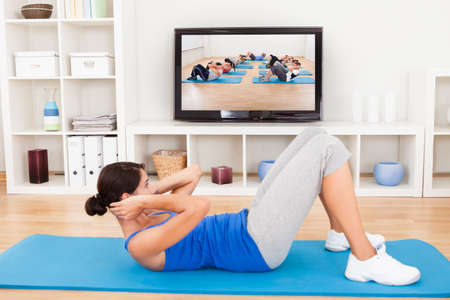 crunch: Young Woman Exercising On Mat In Front Of Television Stock Photo