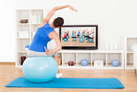 ball stretching: Female Working Out With An Blue Exercise Ball In Front Of Television Stock Photo