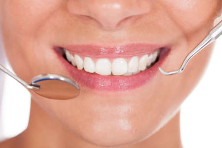 clean teeth: Smiling woman with perfect white teeth and a small dentists mirror reflecting her teeth being held alongside