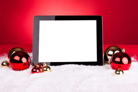 Blank Digital Tablet With Christmas Baubles On Red Background photo