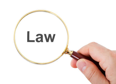 codified: Close-up Of Hand Showing Law Word Through Magnifying Glass Over White Background Stock Photo