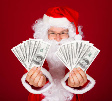 Portrait of happy santa holding dollars over red background photo
