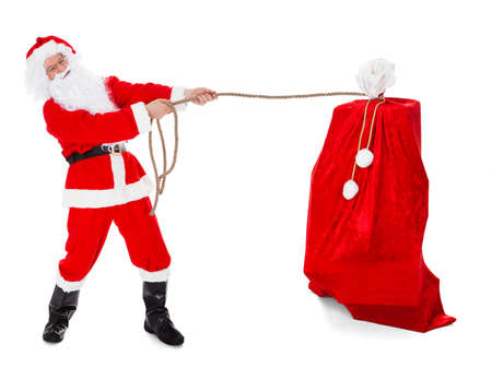 Santa pulling gifts sack over white background photo