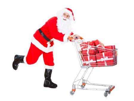 Portrait of santa holding shopping cart on white background photo