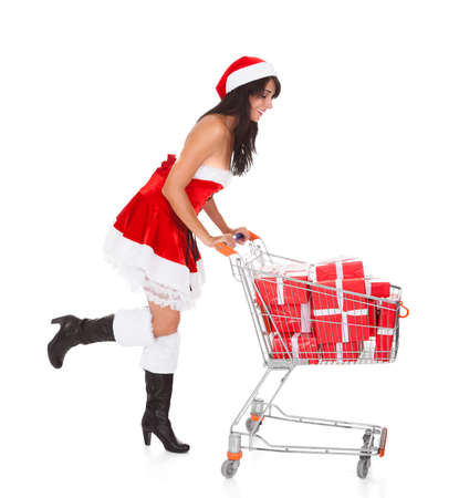 Woman In Santa Claus Pushing Cart With Present Over White Background photo
