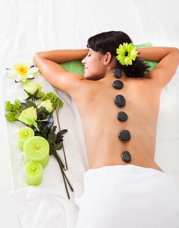 Beautiful Woman Relaxing At A Spa Receiving Hot Stone Massage photo