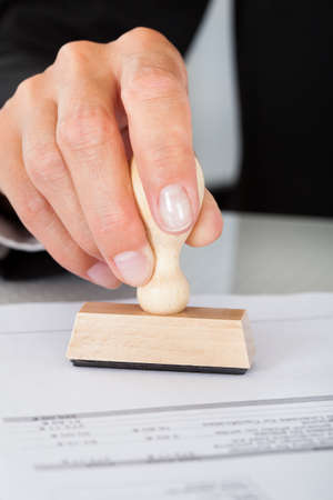 rubber stamp: Close-up Of Business Man Hand Pressing Rubber Stamp On Document