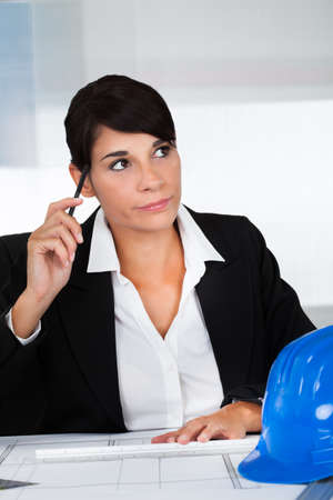Young Happy Female Architect Working On Blue Print In Office Stock Photo - 22887625