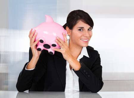 Young Happy Businesswoman Holding Pink Piggy Bank At Desk photo