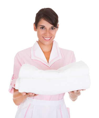 Boldog Nő Maid Holding halom fehér törölköző fölött fehér háttér Stock fotó