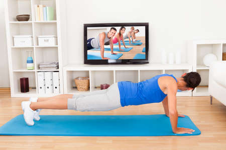 Young Woman Doing Pushup In Front Of Television photo