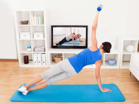 woman fitness: Jeune femme exer�ant sur tapis devant la t�l�vision