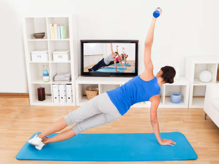 working from home: Young Woman Exercising On Mat In Front Of Television Stock Photo