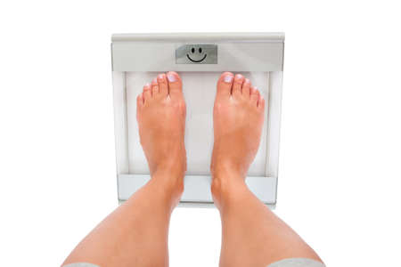 Close-up Of Woman's Feet Measuring Weight Over White Background photo