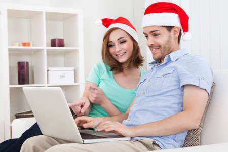 Young happy couple wearing santa hat looking at laptop photo
