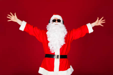 Portrait of excited santa raising his arms on red background photo