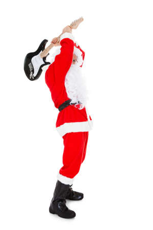 Portrait of a angry santa breaking guitar over white background photo