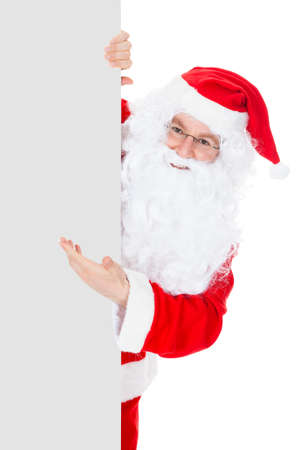 Portrait of a santa holding blank placard over white background photo