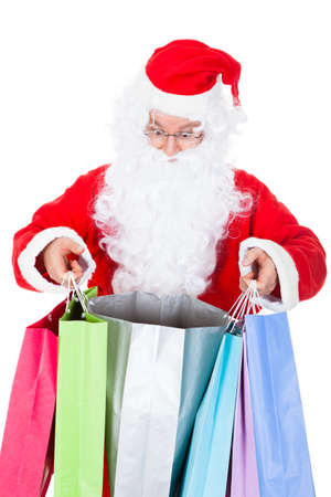 Surprised santa looking inside shopping bag on white background photo