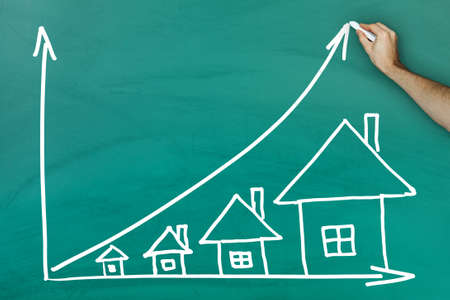 house prices: House prices growth concept on green blackboard Stock Photo