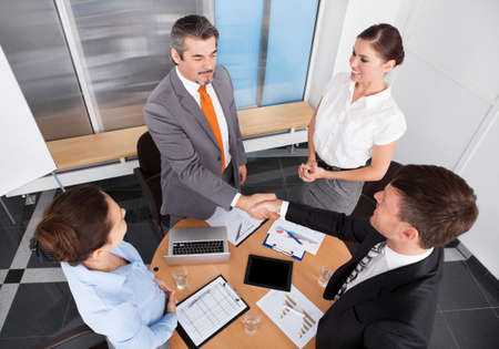 Two Businessmen Shaking Hands In Front Of Colleagues At Office photo