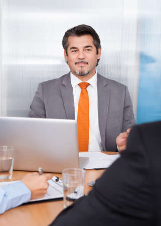 Portrait Of Businessman Discussing In Office Meeting photo