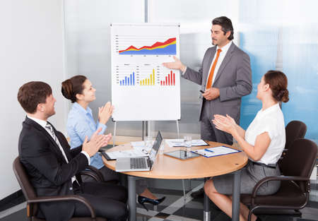 flipchart: Group Of Colleagues Appreciating Businessman At Presentation