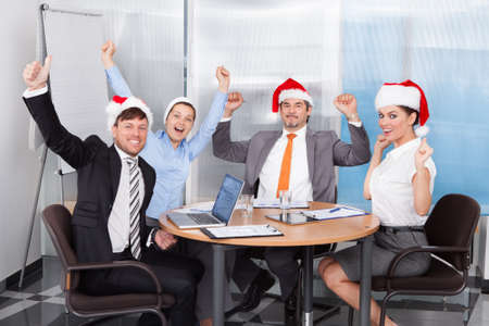 Happy Colleagues In Santa Hat Celebrating Christmas At Office Stock Photo