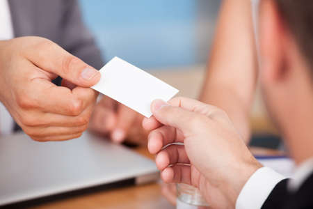 Close-up Of Two Businessmen Holding Card Over Desk Stock Photo