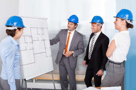 Group Of Architects Discussing Plan Drawn On Blueprint At Office photo