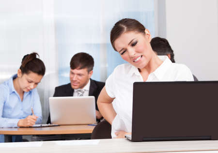 Young Businesswoman Sitting In Front Of Her Colleagues Suffering From Back Pain photo