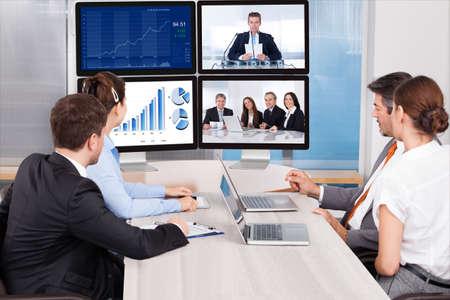 Ondernemers zitten in een vergaderzaal in het computer scherm kijken Stockfoto