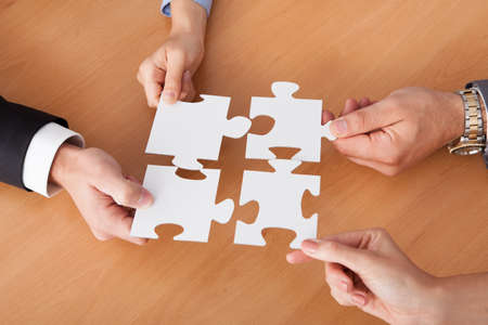 Close-up Of Businesspeople Holding Jigsaw Puzzle Over Desk photo