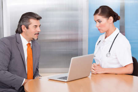 office visit: Happy Businessman And Female Doctor Talking Together Stock Photo