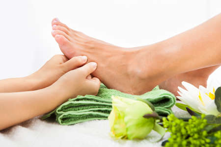 woman foot: Close-up Of Woman Feet Receiving Foot Massage In Spa