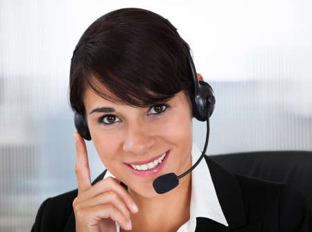 Happy Young Female Callcenter Employee Wearing Headset In Office photo