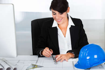 Young Happy Female Architect Working On Blue Print In Office Stock Photo - 23183229