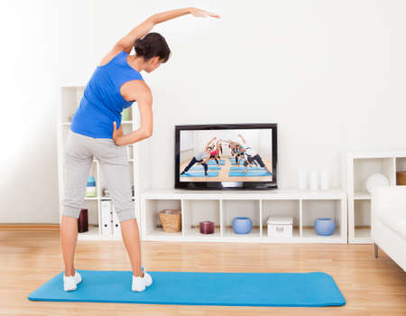 Female Doing Fitness Exercise In Front Of Television Stock Photo - 23183232